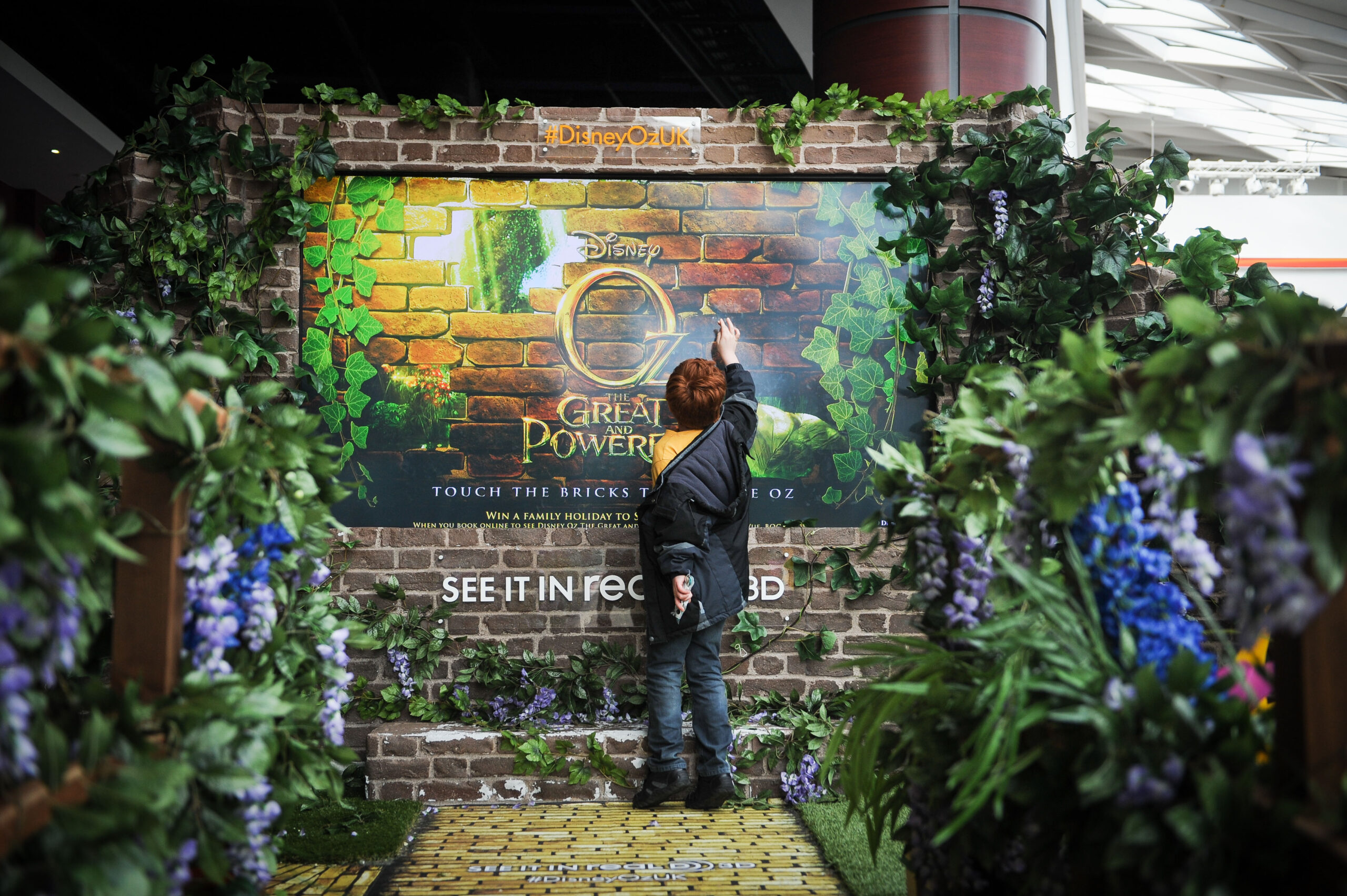 """Vue Entertainment has brought """"Oz World"""" to Vue Westfileld to promote new release, """"Oz The Great and Powerful"""". This  involves the construction of a large yellow brick road running along the balcony in Westfield shopping centre with a bridge, leading to an interactive digital screen. On Saturday there was a magician and assistant in Oz character dress (Victorian costumes) running 'Covent Garden' style magical theatre acts through the day in the foyer area. Pictured are some movie-goers enjoying the entertainment on show.  PICTURES BY DANIEL LEWIS +44(0)7813 987475"""